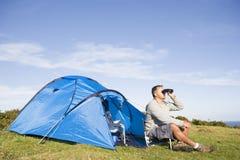 Hombre que acampa al aire libre y que mira con binocular Imágenes de archivo libres de regalías