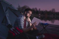 Hombre que acampa por el lago foto de archivo