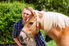Hombre que acaricia el caballo Fotografía de archivo libre de regalías