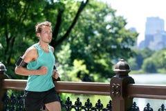 Hombre que activa en Central Park que escucha el funcionamiento de la música Imagen de archivo