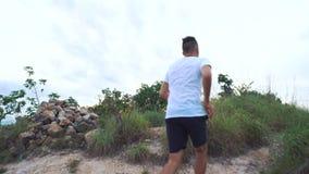 Hombre que activa en el camino de la montaña Muchacho de la aptitud del deporte que ejercita afuera en montaña Forma de vida sana almacen de video