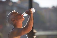Hombre que activa mayor que bebe el agua dulce de la botella Fotografía de archivo