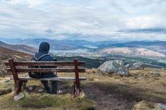 Hombre que admira la opinión del paisaje sobre un banco imagenes de archivo