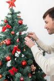 Hombre que adorna el árbol de navidad Imagen de archivo libre de regalías