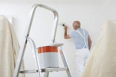 Hombre que adorna el sitio con la poder de la pintura y del cepillo en primero plano Fotografía de archivo libre de regalías