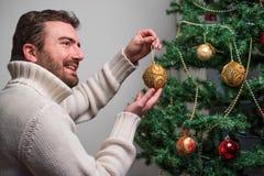 Hombre que adorna un árbol de navidad con las bolas de oro Imagenes de archivo
