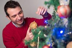 Hombre que adorna un árbol de navidad con las bolas de oro Imagen de archivo