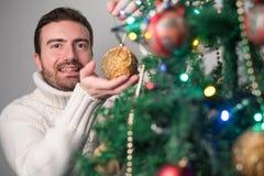 Hombre que adorna un árbol de navidad con las bolas de oro Fotografía de archivo libre de regalías