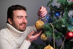 Hombre que adorna un árbol de navidad con las bolas de oro Foto de archivo
