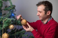 Hombre que adorna un árbol de navidad con las bolas de oro Imágenes de archivo libres de regalías