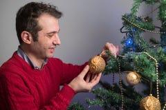 Hombre que adorna un árbol de navidad con las bolas de oro Imagen de archivo libre de regalías