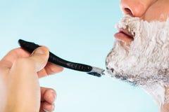 Hombre que afeita con perfil de la cara de la maquinilla de afeitar Imagenes de archivo