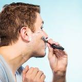 Hombre que afeita con perfil de la cara de la maquinilla de afeitar Imágenes de archivo libres de regalías