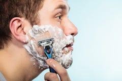 Hombre que afeita con perfil de la cara de la maquinilla de afeitar Foto de archivo