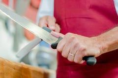 Hombre que afila el cuchillo con acero imagen de archivo libre de regalías