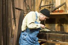 Hombre que afila una sierra vieja Imagen de archivo