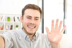 Hombre que agita en una llamada video en casa Fotos de archivo libres de regalías