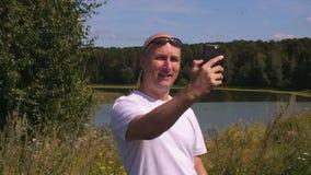 Hombre que agita y que muestra el pulgar para arriba mientras que teniendo charla video en el teléfono almacen de video
