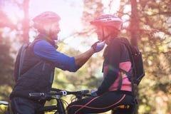 Hombre que ajusta el casco de la bicicleta de la mujer Imagen de archivo
