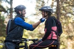Hombre que ajusta el casco de la bicicleta de una mujer Imagen de archivo libre de regalías