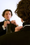 Hombre que ajusta el lazo en el espejo Fotos de archivo