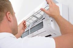 Hombre que ajusta el sistema de aire acondicionado Fotos de archivo