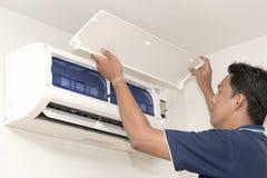 Hombre que ajusta el sistema de aire acondicionado Imágenes de archivo libres de regalías