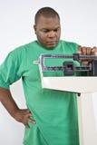 Hombre que ajusta la escala del peso en la clínica Fotos de archivo libres de regalías