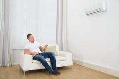 Hombre que ajusta la temperatura del acondicionador de aire imagen de archivo libre de regalías
