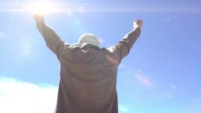 Hombre que alcanza el top de montañas Aumente para arriba las manos Concepto del logro, euforia Contra el cielo azul En el día so almacen de metraje de vídeo