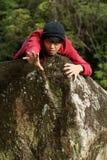 Hombre que alcanza hacia fuera el brazo sobre roca Fotos de archivo