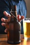 Hombre que alcanza para la cerveza Fotos de archivo libres de regalías