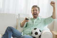 Hombre que anima mientras que mira el partido de fútbol en casa Fotos de archivo