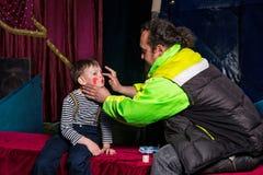 Hombre que aplica al payaso Make Up a la cara de los muchachos Imagen de archivo libre de regalías