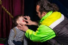 Hombre que aplica al payaso Make Up a la cara de los muchachos Foto de archivo libre de regalías