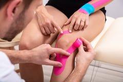 Hombre que aplica la cinta de la kinesiolog?a en la rodilla de la mujer foto de archivo