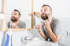 Hombre que aplica la crema de la crema hidratante en cuarto de ba?o fotografía de archivo libre de regalías