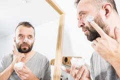 Hombre que aplica la crema de la crema hidratante en cuarto de ba?o fotos de archivo libres de regalías