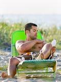 Hombre que aplica la loción de la protección solar en la playa Foto de archivo