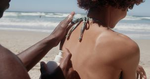 Hombre que aplica la protección solar en hombros de la mujer en la playa 4k almacen de video
