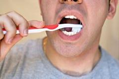 Hombre que aplica sus dientes con brocha Imagen de archivo