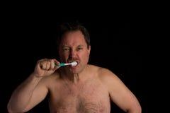 Hombre que aplica sus dientes con brocha Imágenes de archivo libres de regalías