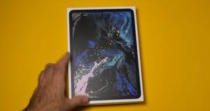 Hombre que arregla en tableta elegante del último iPad de la tabla la favorable almacen de metraje de vídeo