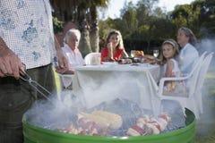 Hombre que asa a la parrilla con la familia en la tabla al aire libre Foto de archivo libre de regalías