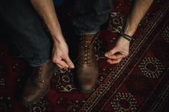 Hombre que ata encima de sus botas Fotografía de archivo libre de regalías