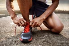 Hombre que ata las zapatillas deportivas Fotos de archivo libres de regalías