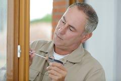 Hombre que atornilla y que repara el tirador de puerta fotos de archivo