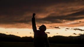 Hombre que aumenta su puño contra el cielo de la puesta del sol Fotos de archivo