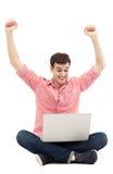 Hombre que aumenta sus brazos delante del ordenador portátil Foto de archivo