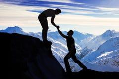 Hombre que ayuda al amigo masculino en roca que sube Fotos de archivo